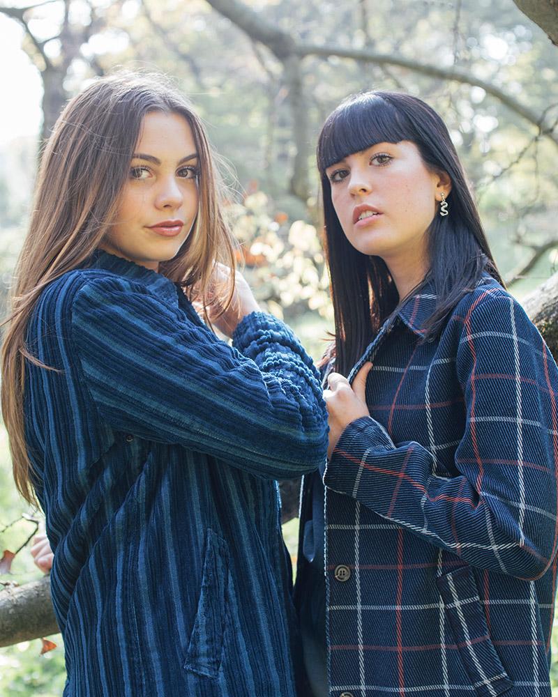 Two girls wearing blue top posing