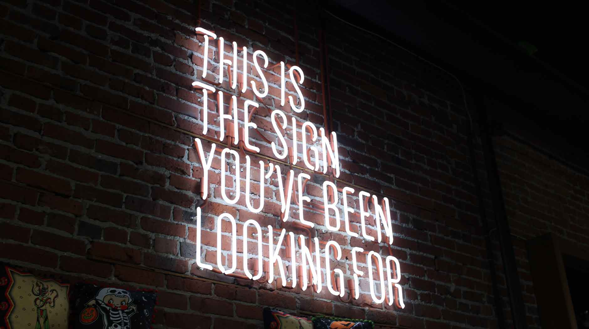 """A neon sign saying, """"this is the sign you've been waiting for."""""""
