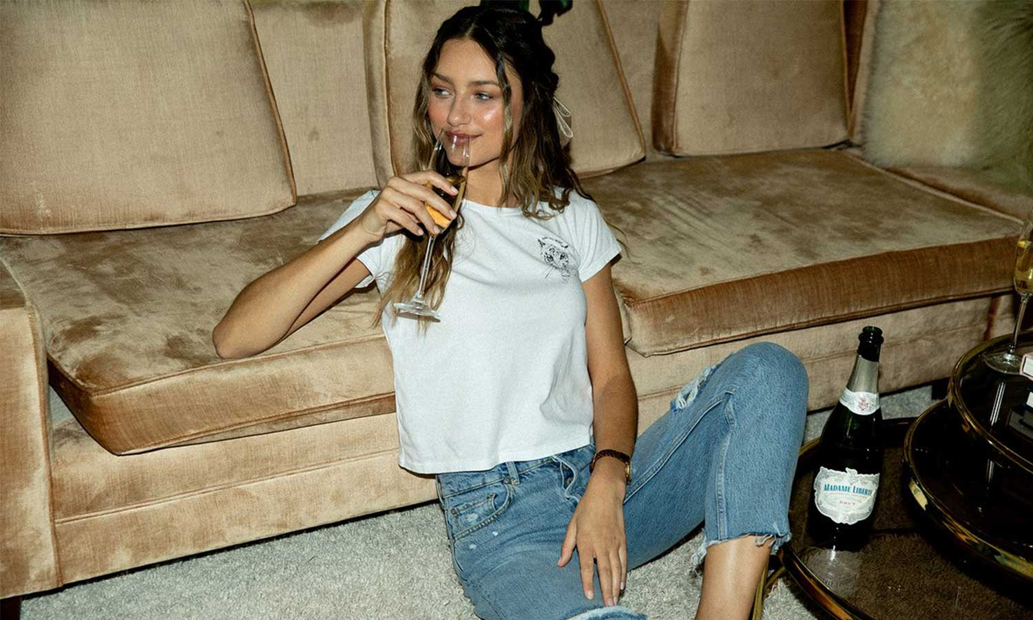 Girl on the floor sipping a glass of champagne