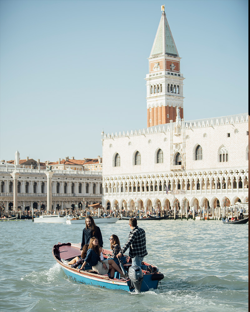 People on a small boat traveling around Venice