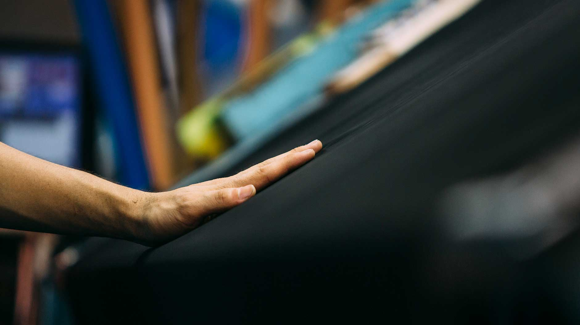 A person touching denim fabric