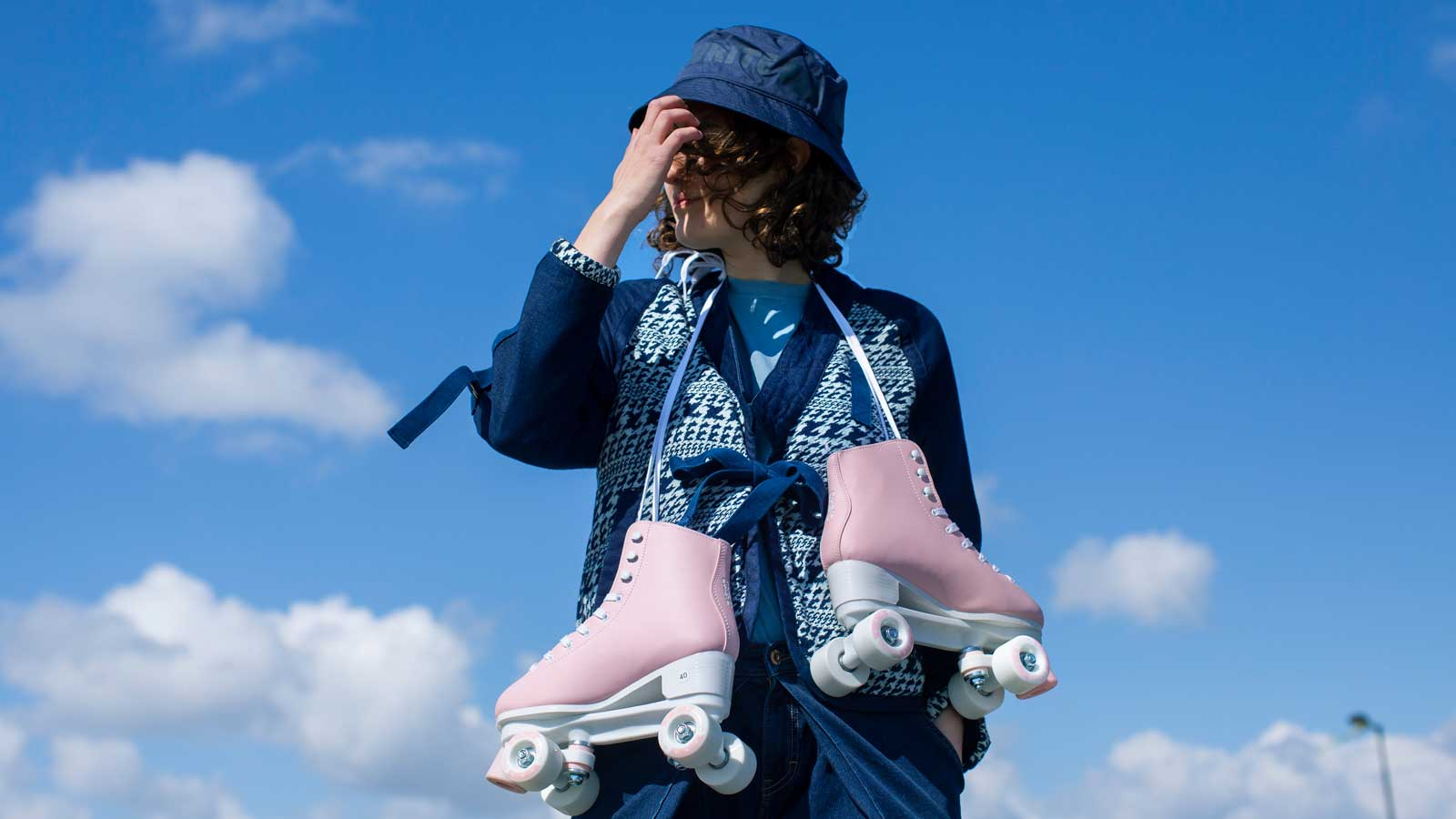 Woman in denim jacket with a pair of roller skates around her neck