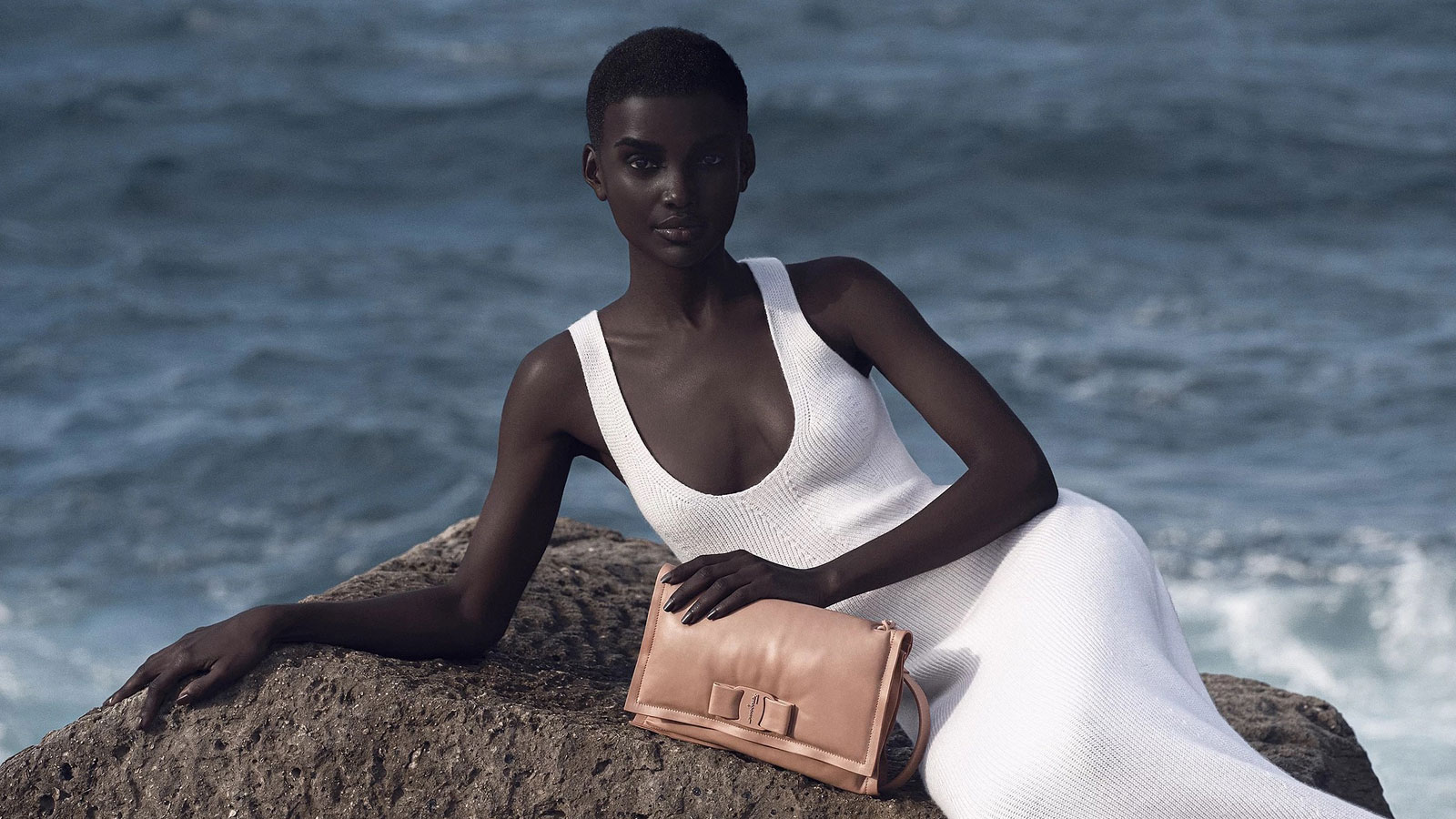 3D model posing next to a beach with a bag wearing a white dress