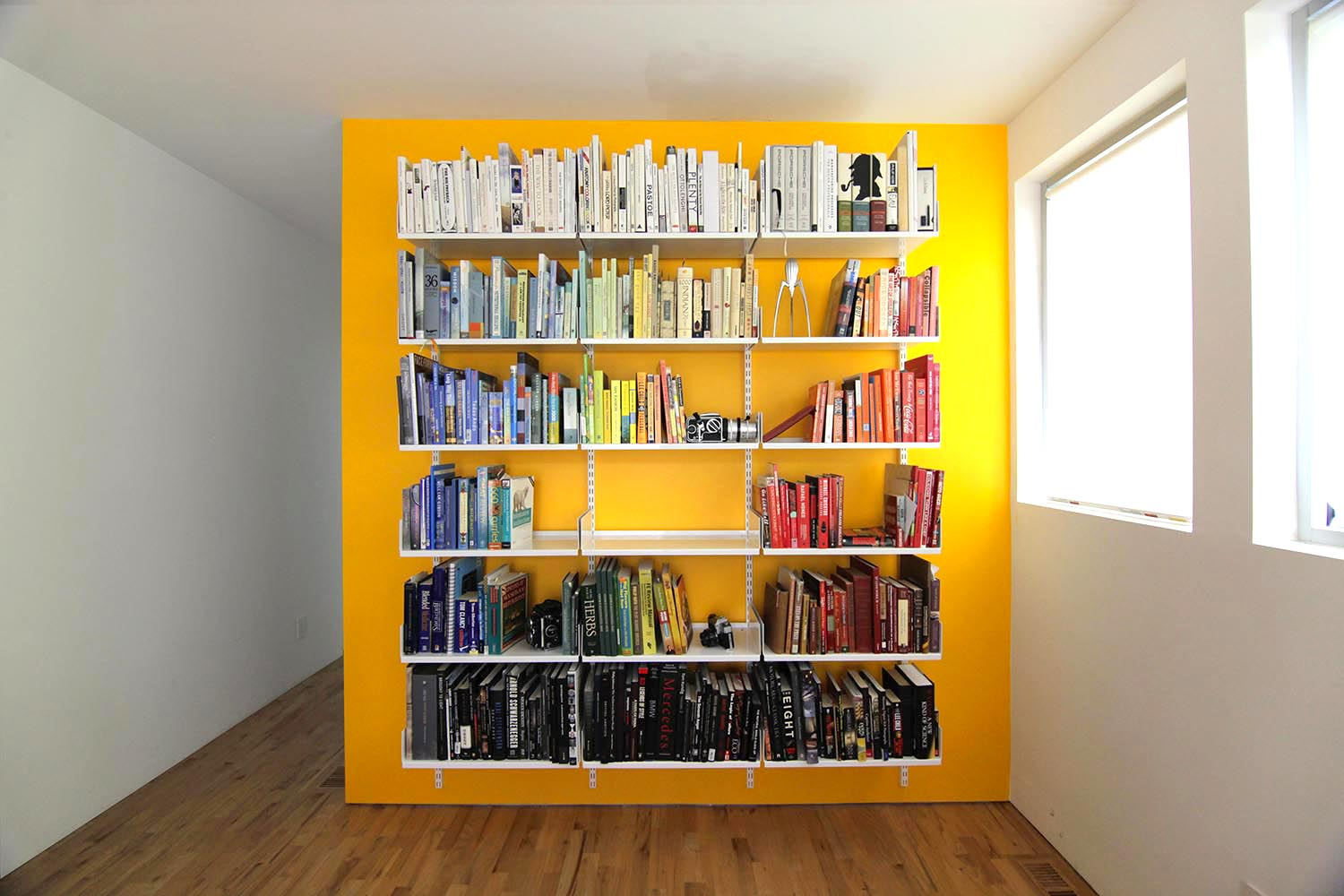 modular shelving system on bright wall color yellow