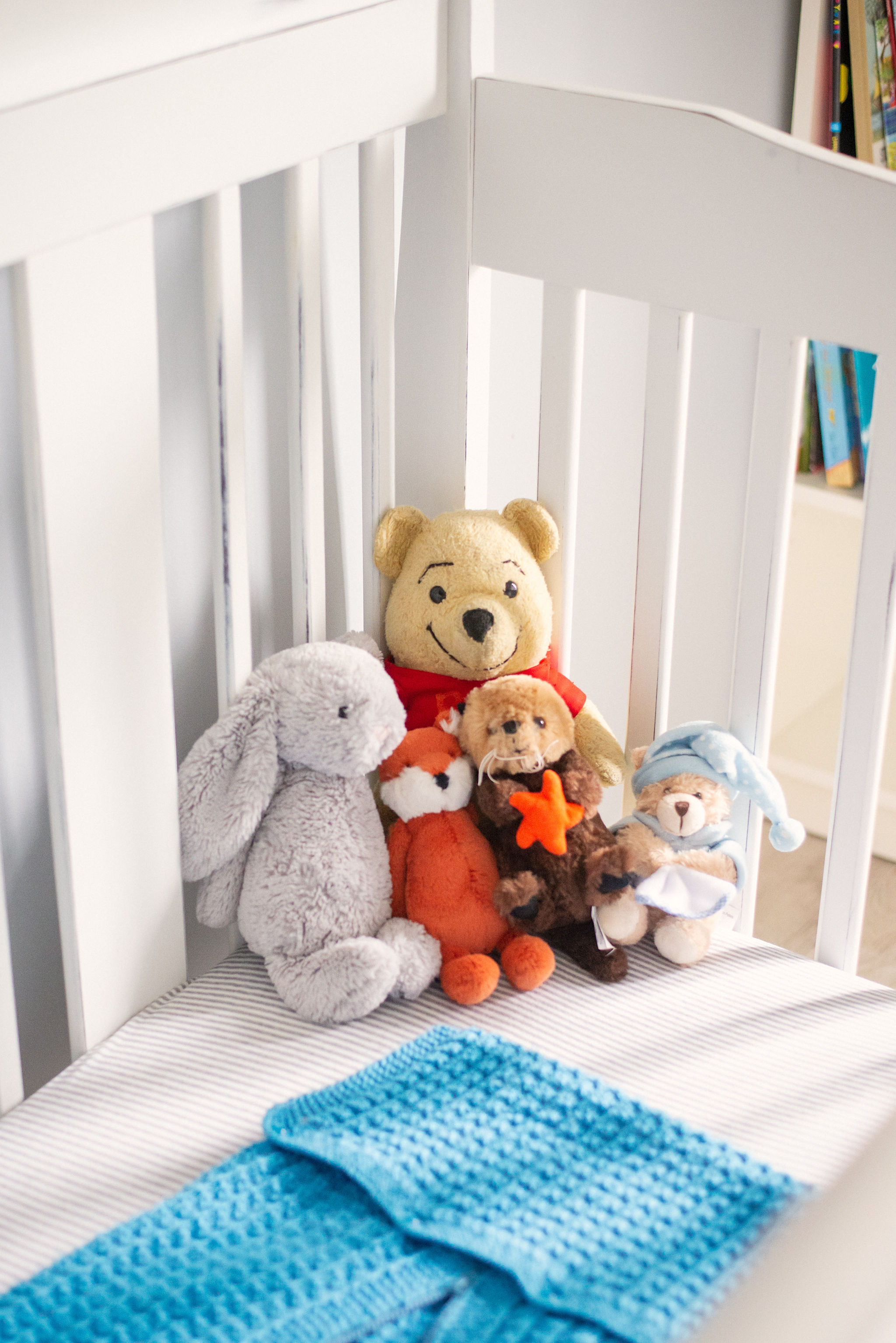Cute stuffed animals sitting up against the inner corner of a baby crib.