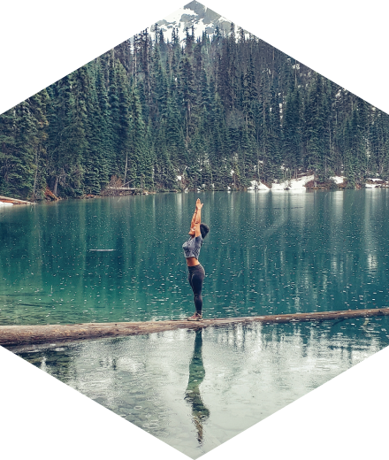 girl balancing on a log in a lake