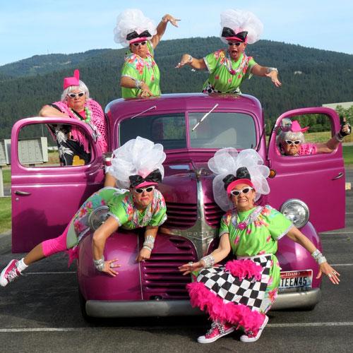 Women posing on pink classic truck