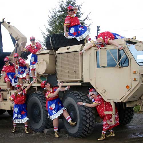 Women posting in costume with military vehicle