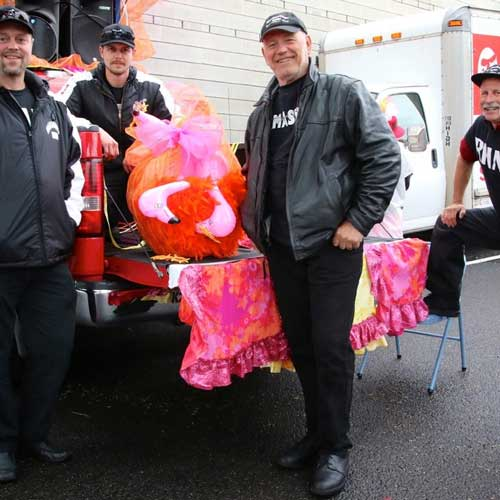 Men standing behind truck with pink flamingo props