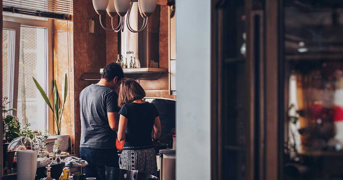 photo of a happy couple cooking in their kitchen