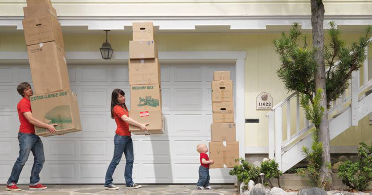 Man, Woman and Child Carrying Stacks of Boxes