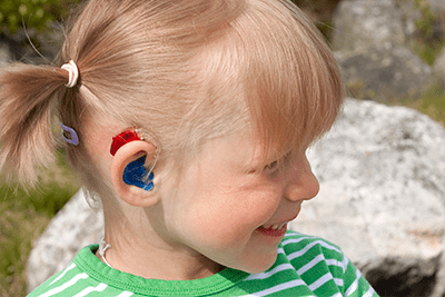 Young girl child with hearing aid