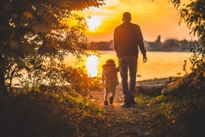 Photo of Father and Child walking in a Sunset