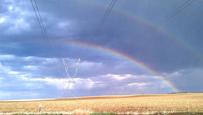 Rainbow arching over a transmission line
