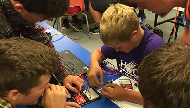 学生们聚集在一起工作一个电路