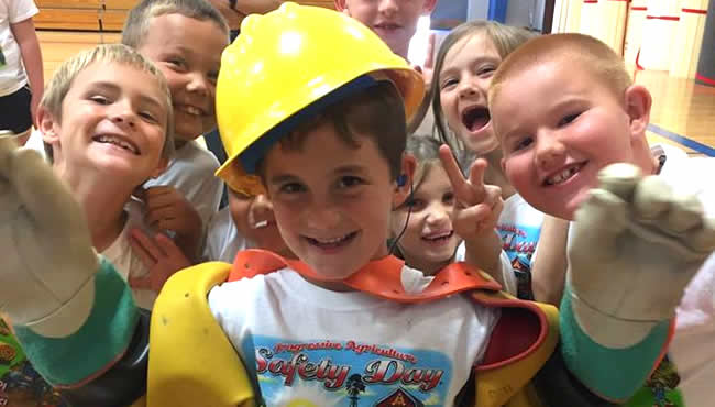 One student wearing a hard hat and gloves with group of students smiling in background
