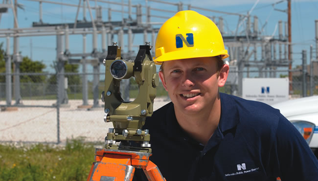 Surveyor with a substation in background