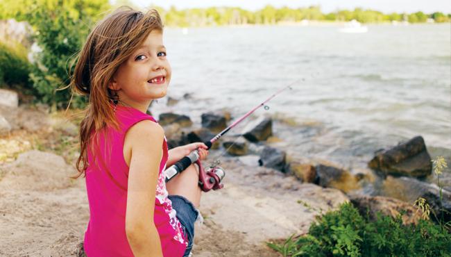 Girl sitting on banks of river fishing