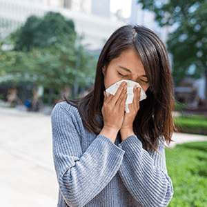Woman sneezing into tissue outdoors