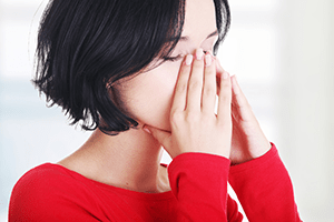 Woman with hands on her face because of sinus pain