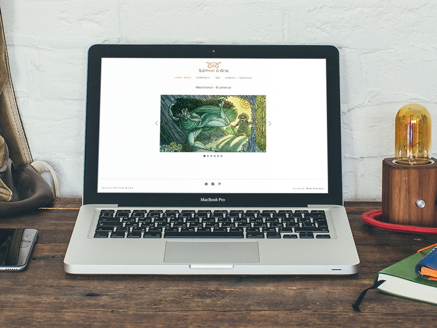 Example Image of custom eCommerce website design on laptop on timber table in small office, displaying graphic design and prints of Kerry based designer