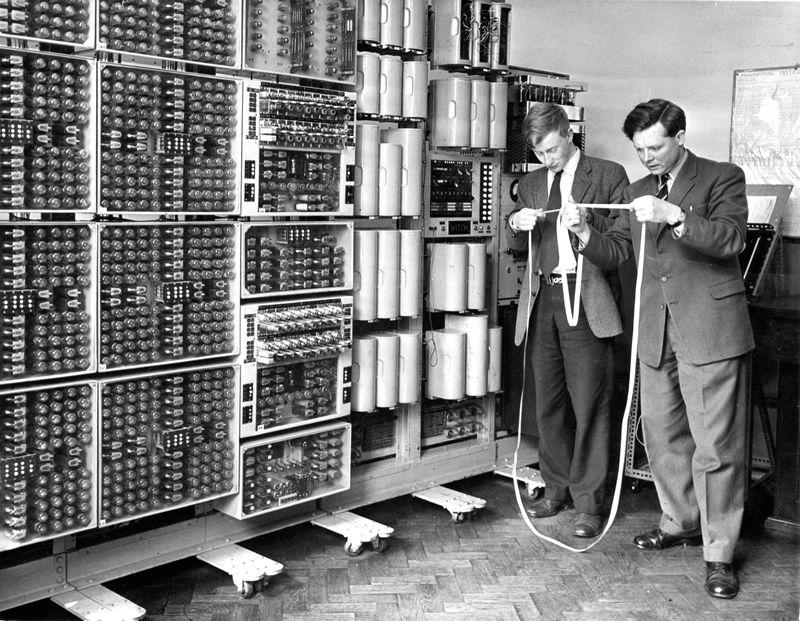 The WITCH at Wolverhampton. Ein Mainframe Computer so gross wie ein Wohnzimmer. Zwei Männer werten Papierstreifen aus, welcher die Maschine druckt.