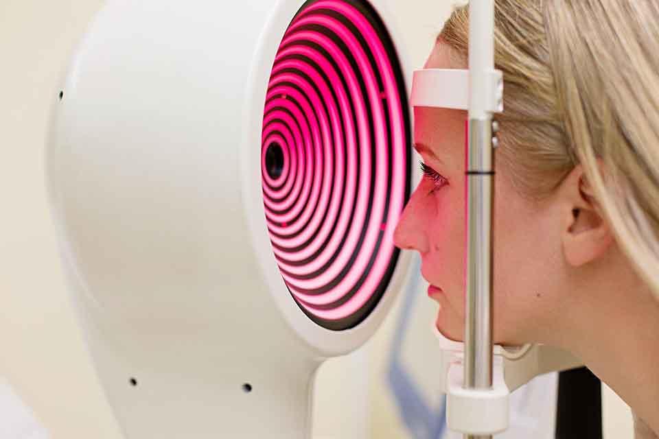 Woman looking into high tech eye scanner