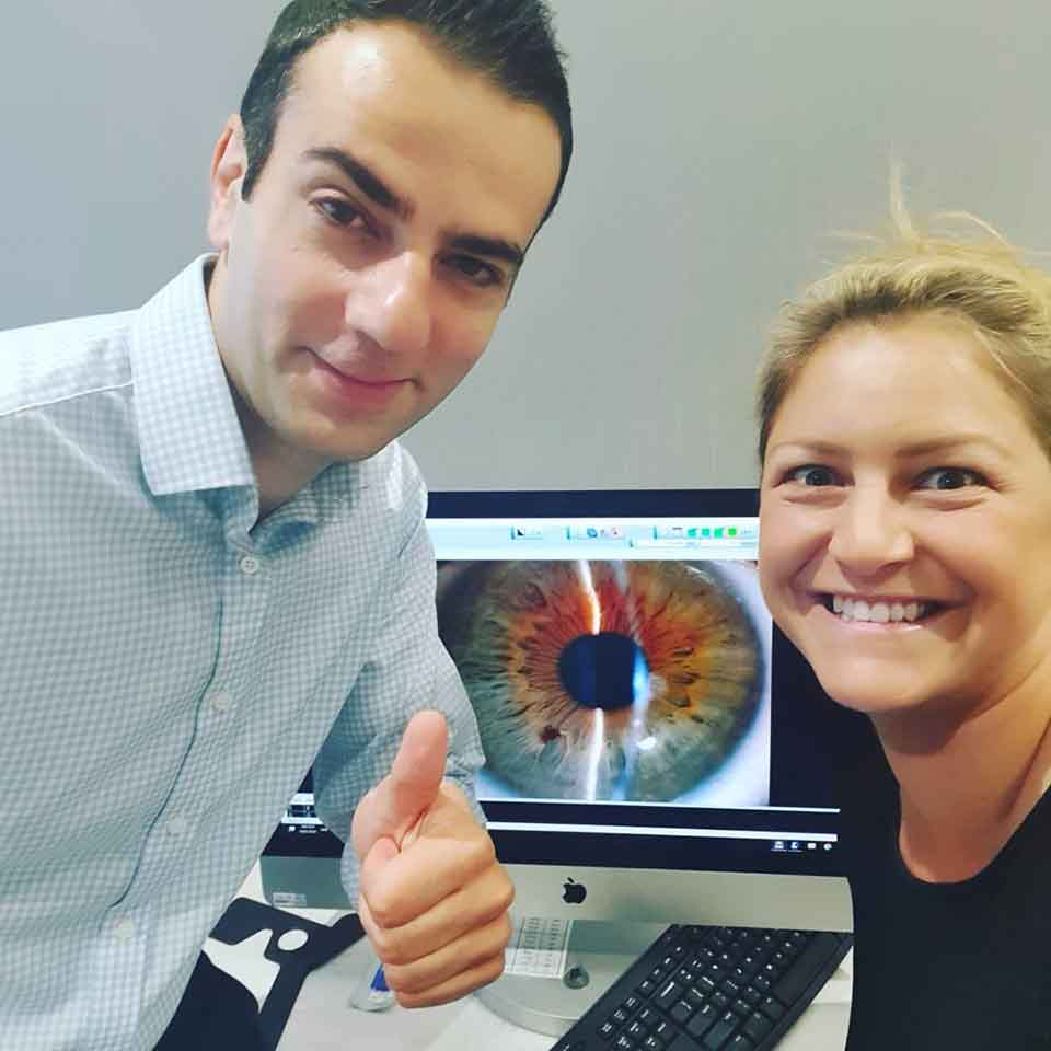 Dr Mo Ziaei and Toni Street smiling at the camera with a photo of Toni's eye on a screen behind them, after Toni's successful laser eye surgery procedure