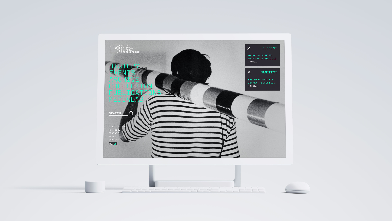 Desktopcomputer mit Ansicht der Startseite des MNAC vor grauem Hintergrund