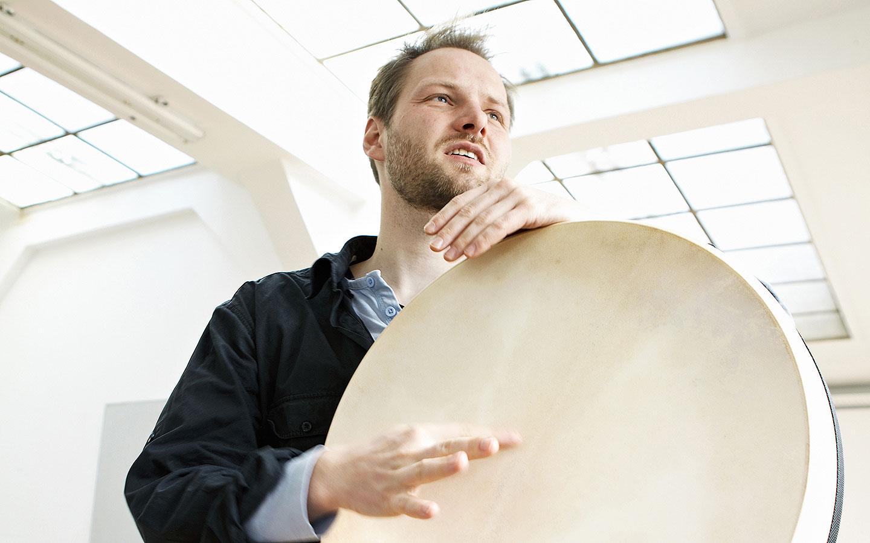 Mann in hellem Raum, der in die Ferne schaut und Rahmentrommel spielt