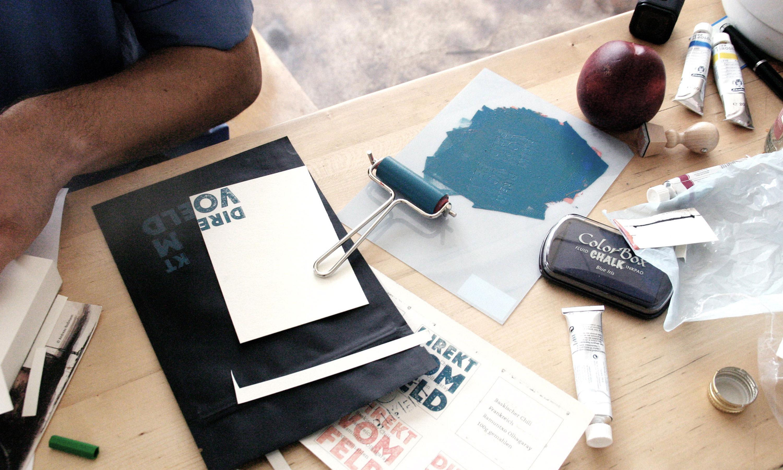 Tisch mit Bastelutensilien, farbige Stempeldrucke des Logos auf verschieden-farbigen Papier