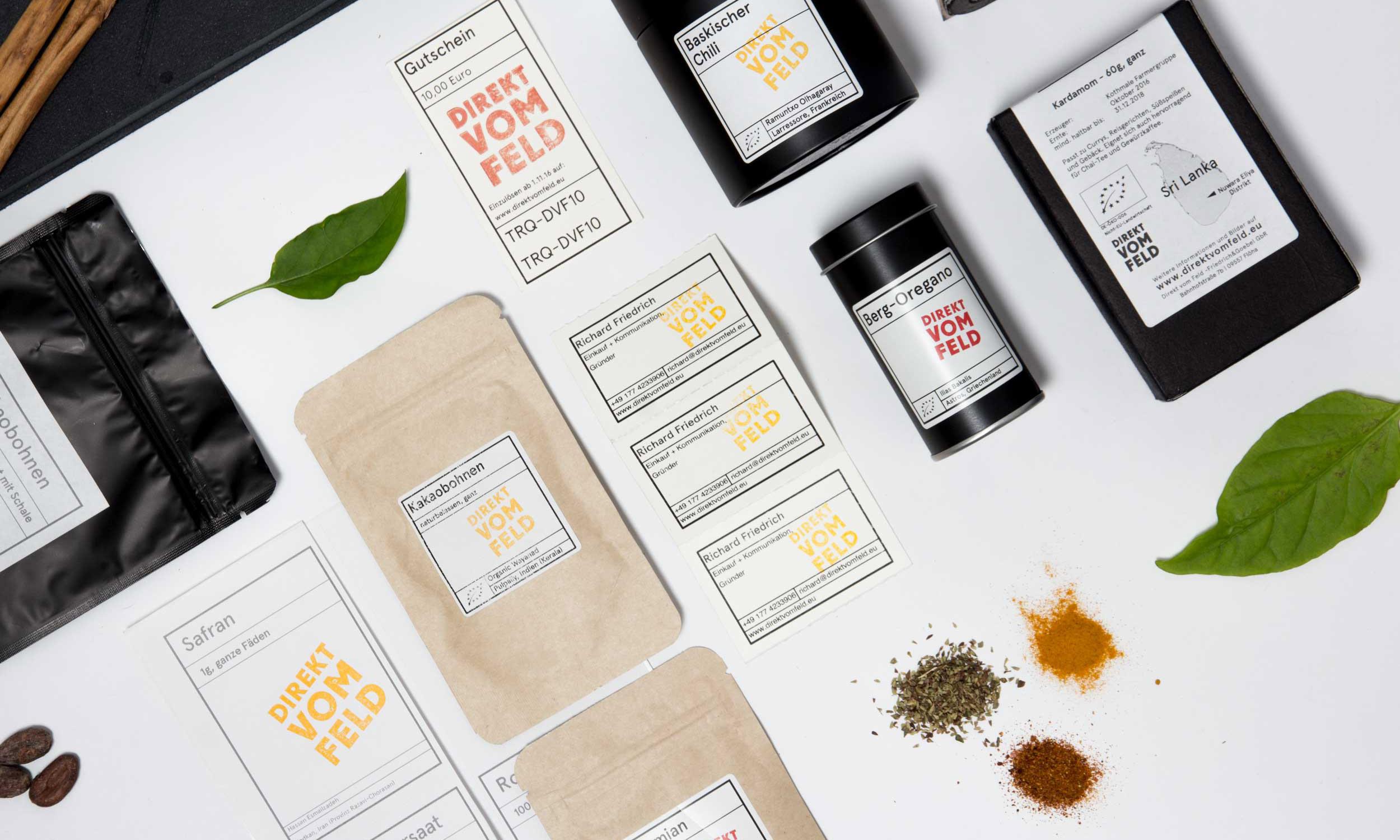 Gewürzverpackungen und Etiketten mit dem neuen Logo auf weißem Hintergrund mit Blättern von Kräutern und ausgestreuten Gewürzen