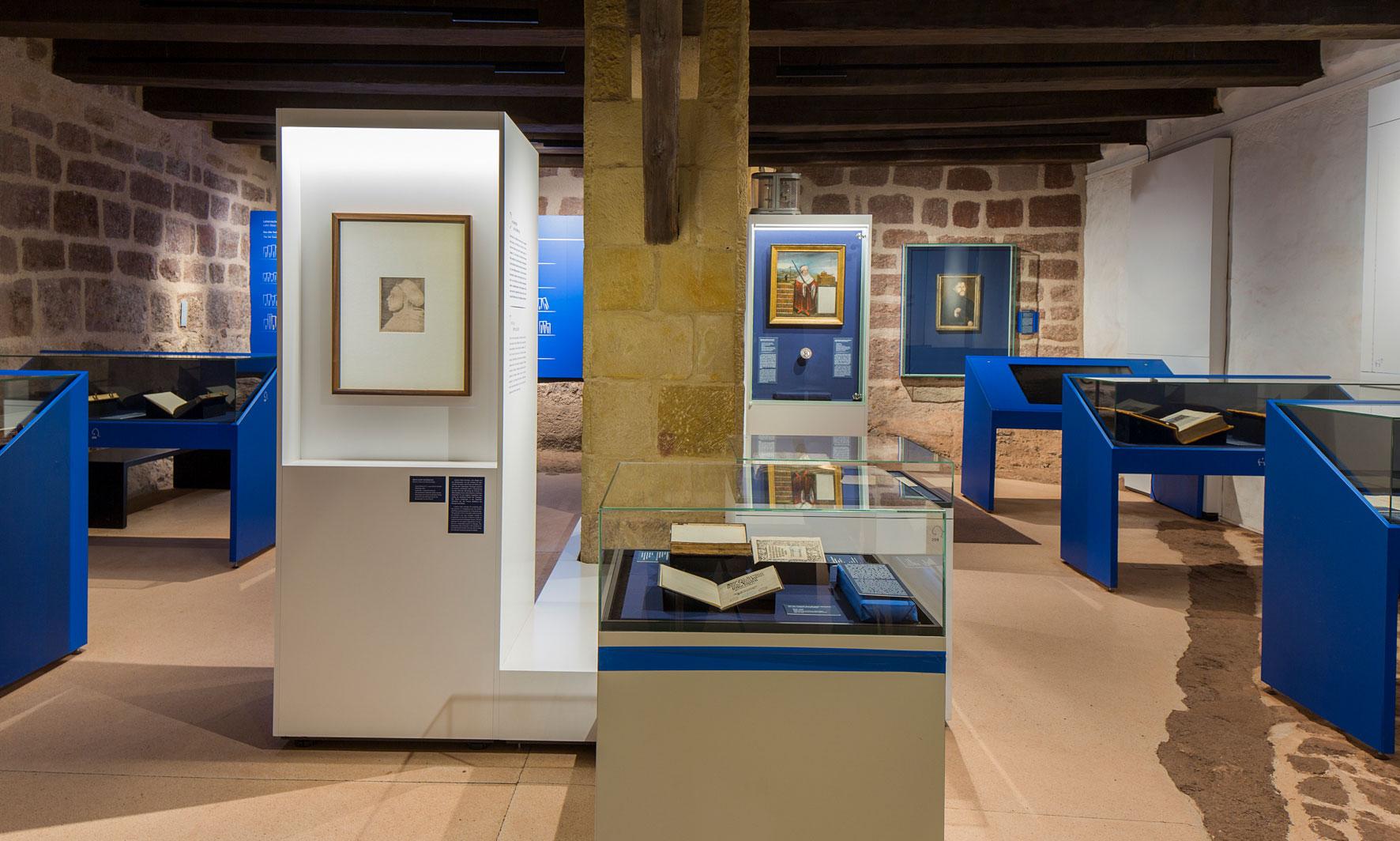Innenaufnahme der Ausstellungsräume, Vitrinen mit verschiedenen Ausstellungsstücken, alte Bücher, Portraits, Touchscreens und Begleittexte
