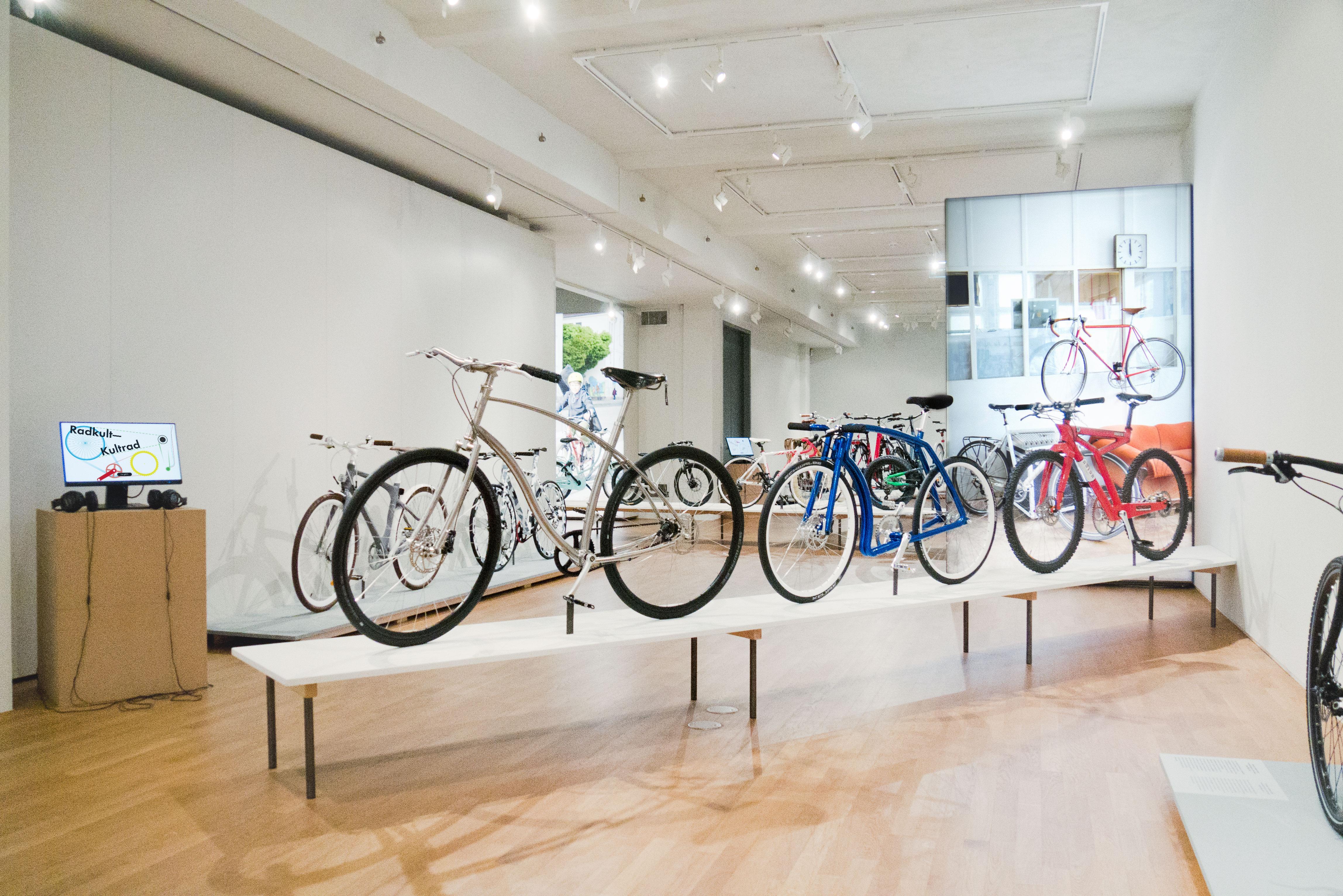 Innenaufnahme der Ausstellung mit Fahrrädern die extravagante Rahmenformen haben