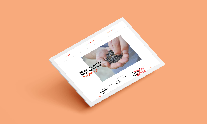 angewinkeltes Tablet auf blass-orangenem Hintergrund mit der Ansicht des Startseite des Webshops