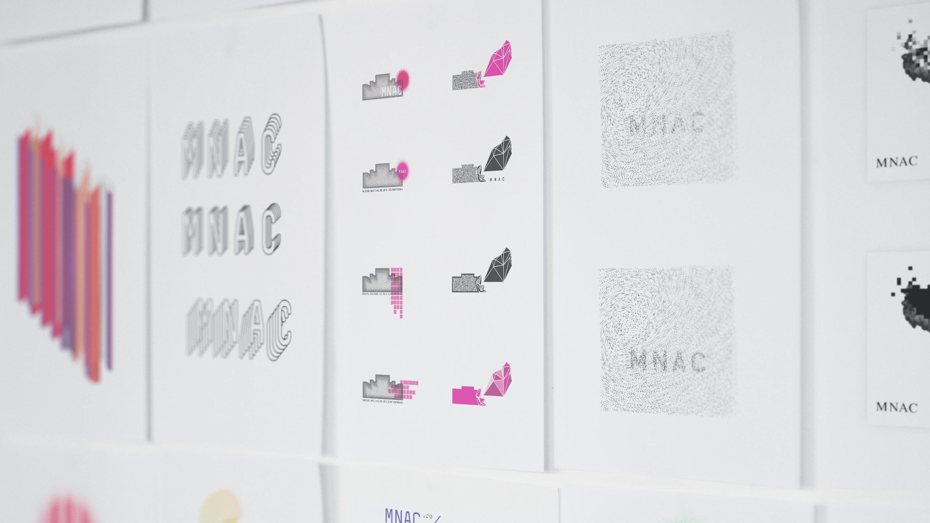 mehrere an die Wand geklebte Ausdrucke von verschiedenen Logo-Entwürfen