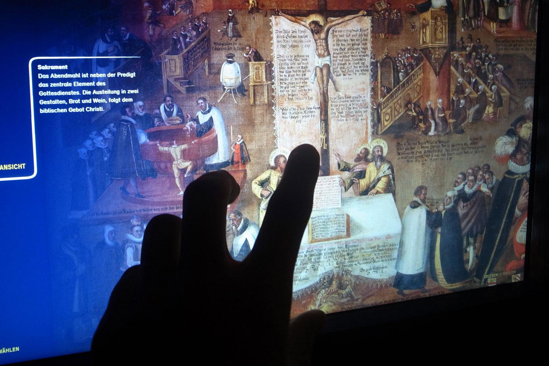 Foto von Hand die auf ein Detail des alten Gemälde im Touchscreen tippt