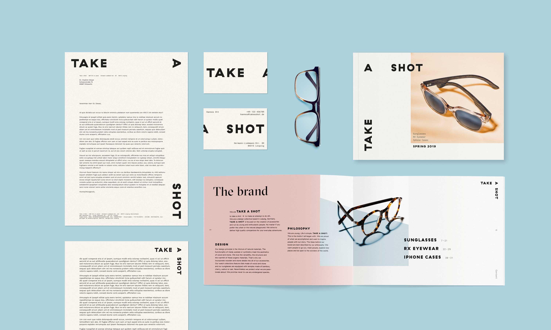 Übersicht auf hellblauen Hintergrund mit einer Brille, den Briefbögen, Visitenkarten und Musterkatalog
