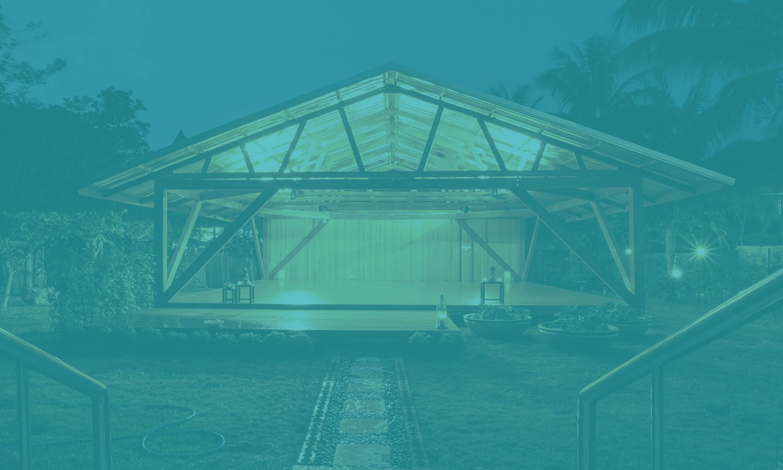 großer überdachter und nach aussen offener Trainingsraum in einem Garten, dahinter Palmen und Dämmerung, davor schwebend das Logo