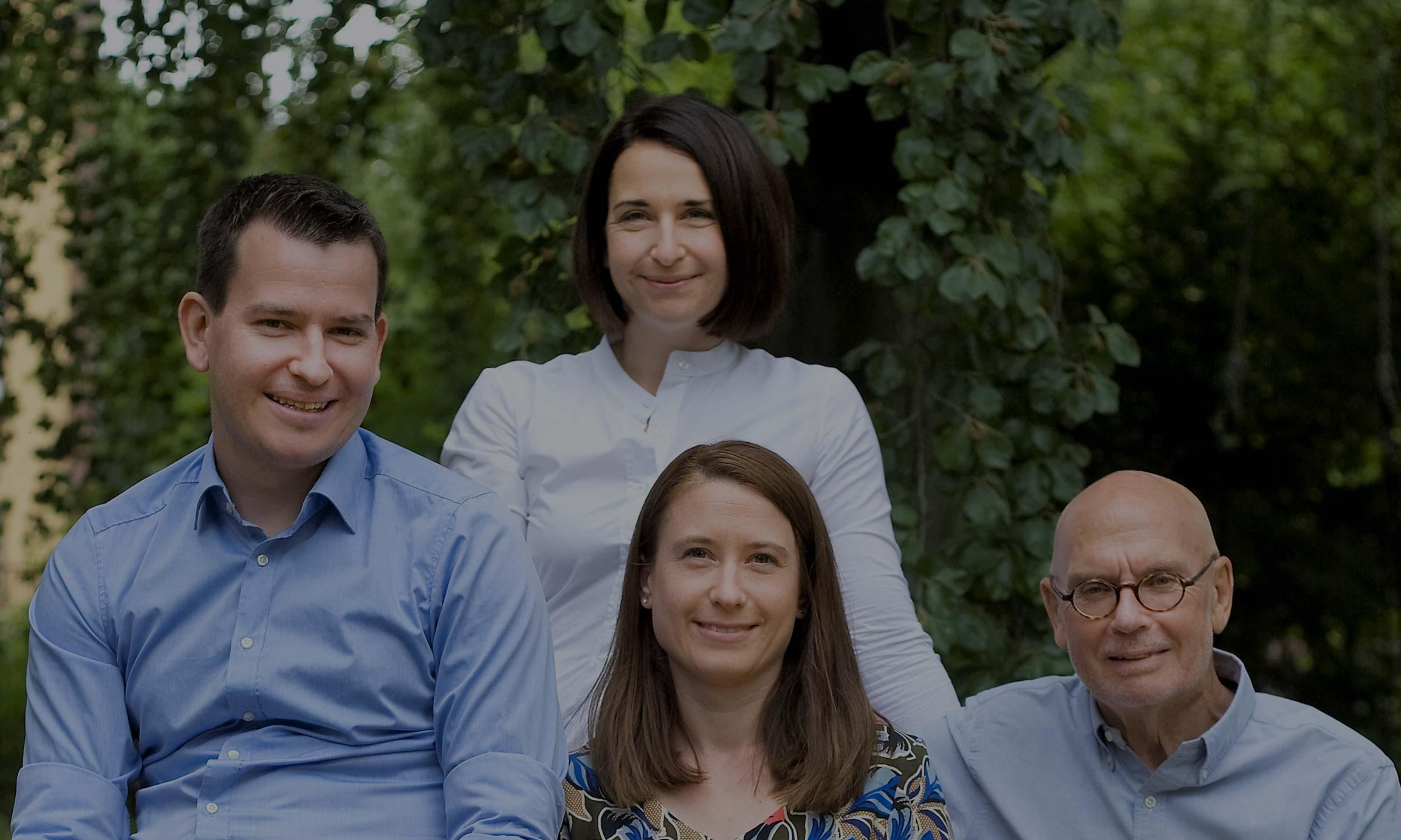 4 lächelnde Personen mit Garten im Hintergrund. Davor das Logo von Golzern Holding