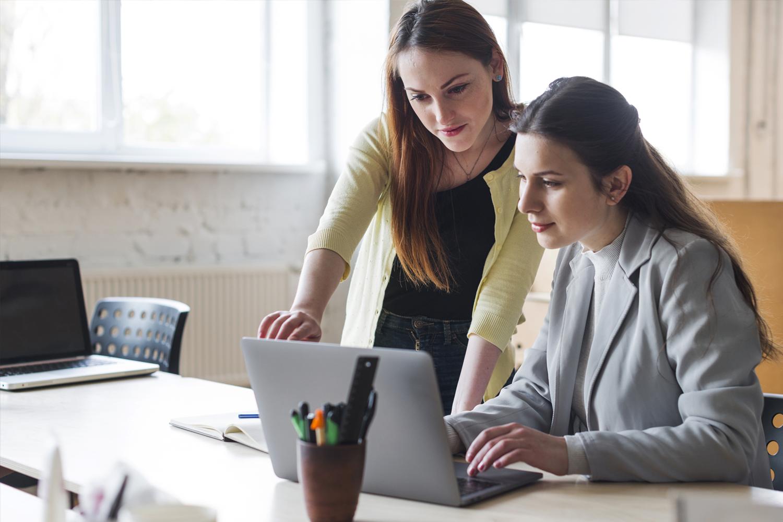 Dos mujeres trabajando en una laptop.