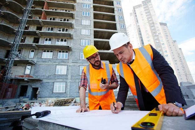 Personas revisando los planos en una construcción.