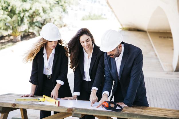 3 personas revisando planos arquitectónicos.