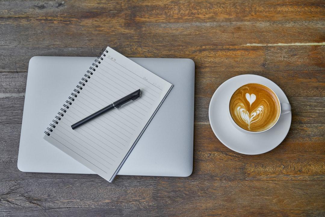 MacBook, cuaderno y café.