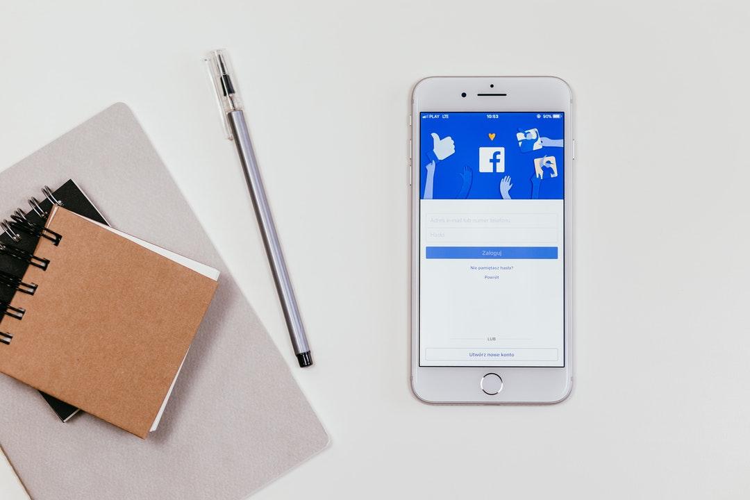 Celular con Facebook, cuaderno y lapicero.