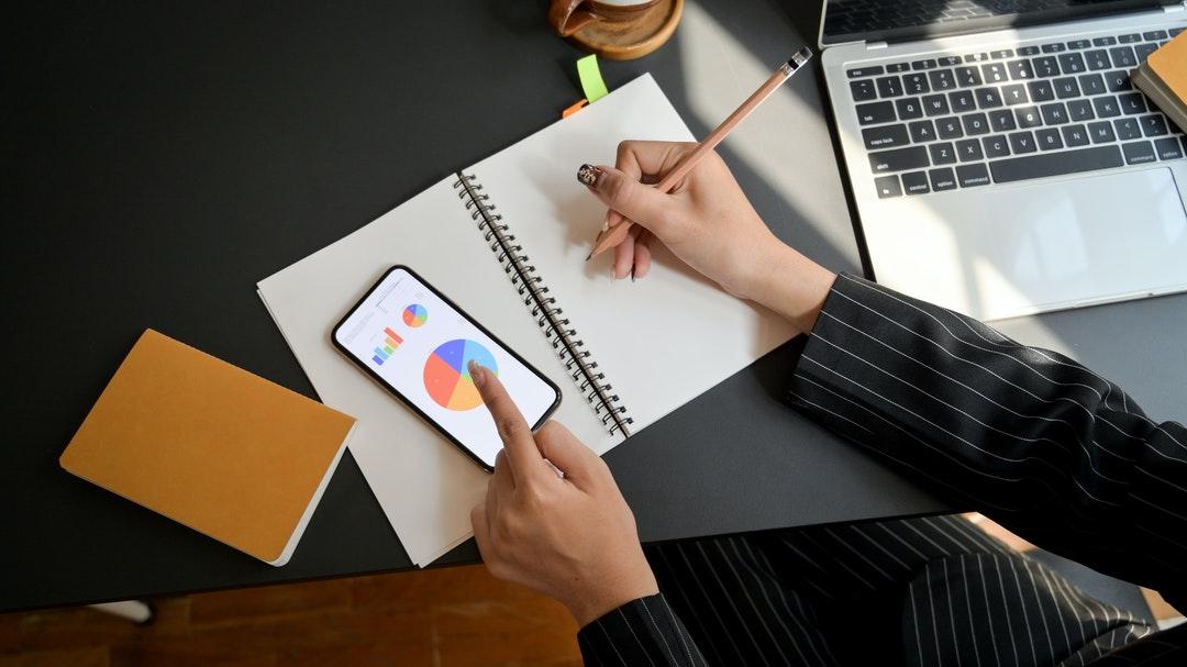 Persona viendo gráficos en su celular y haciendo apuntes.