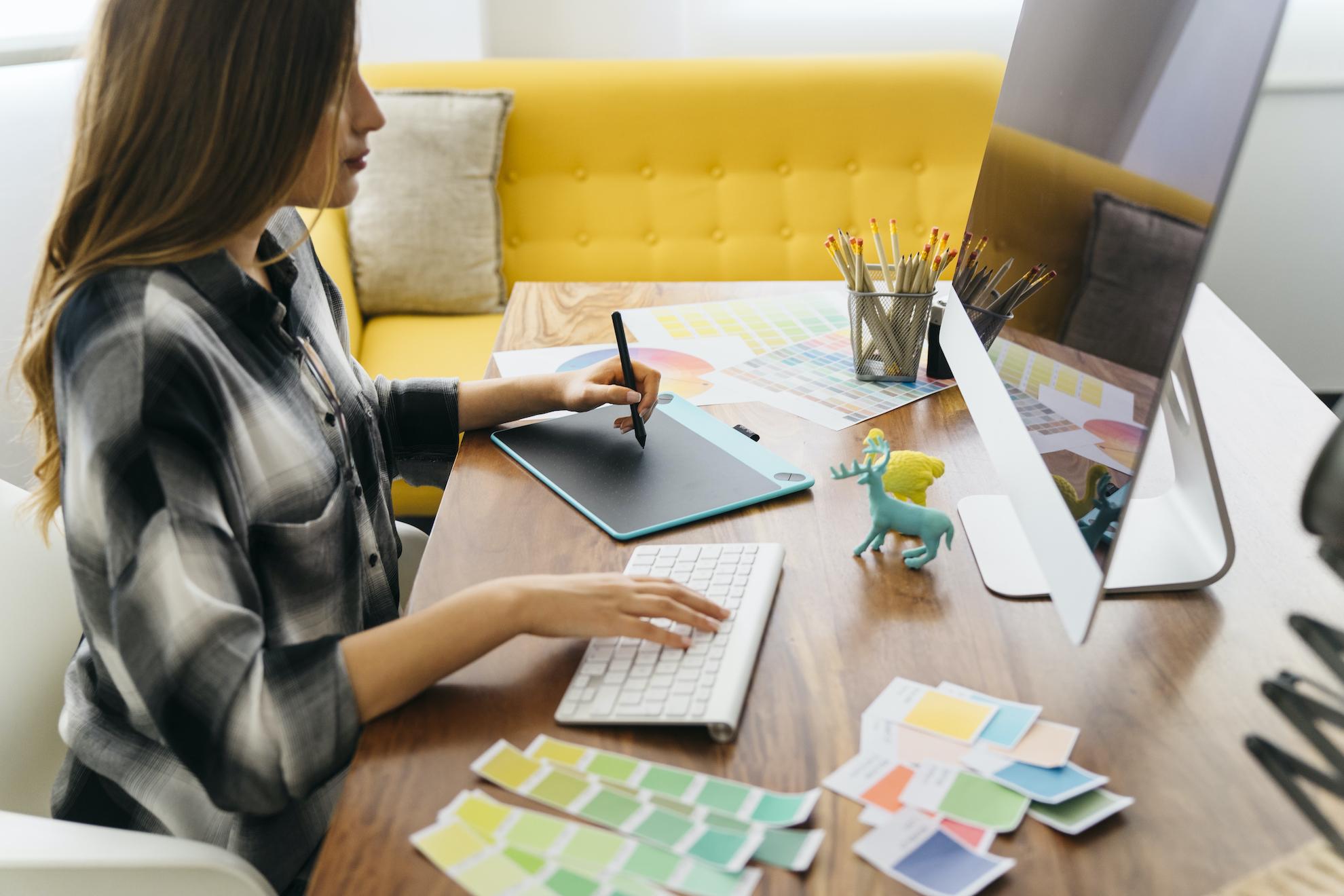 Mujer trabajando en un escritorio con una tableta y una computadora.