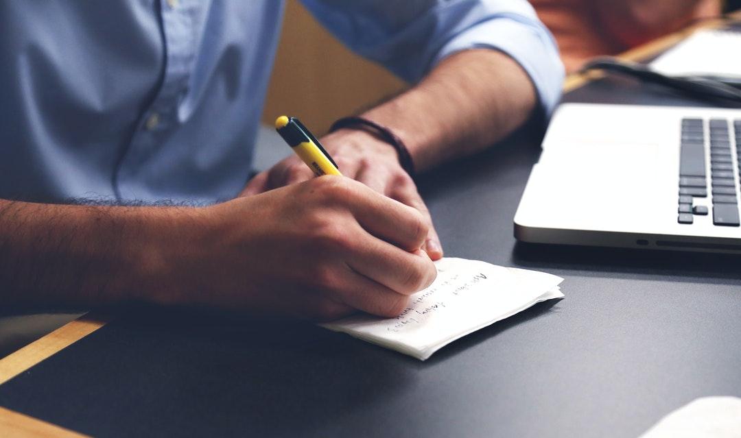 Persona escribiendo notas.