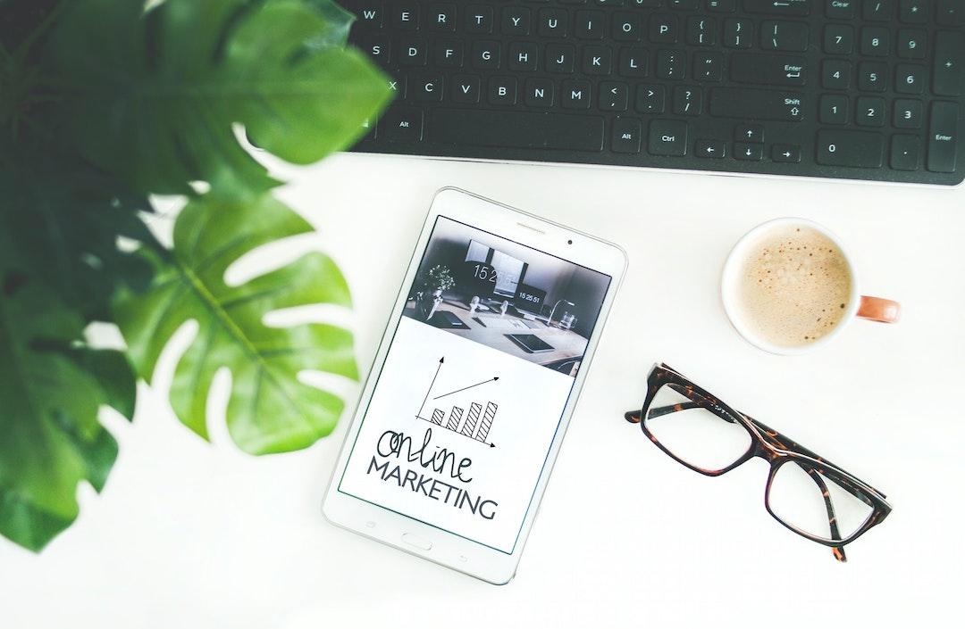 """Celular que dice """"online marketing"""", junto con un teclado, café y lentes."""