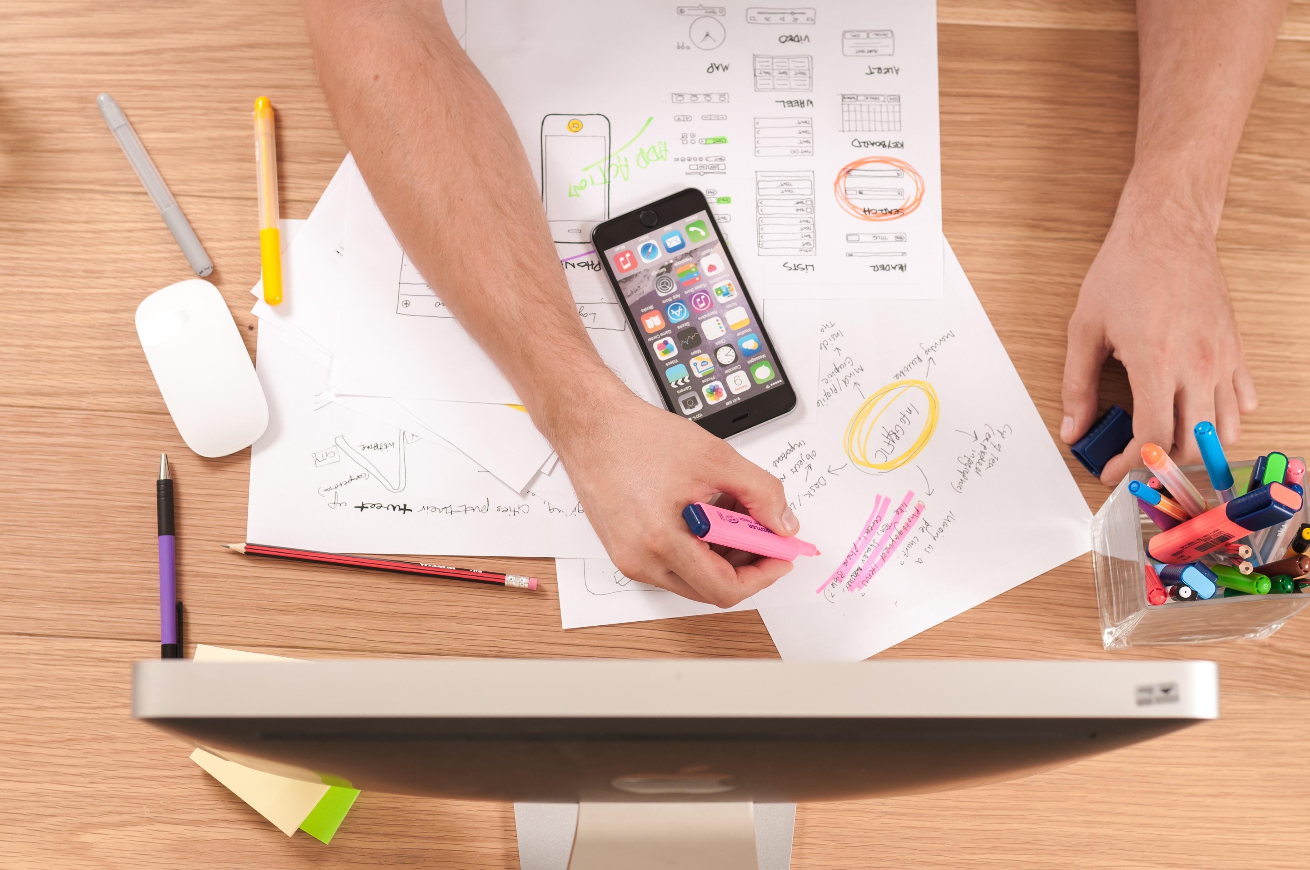 Celular y hojas de papel sobre escritorio